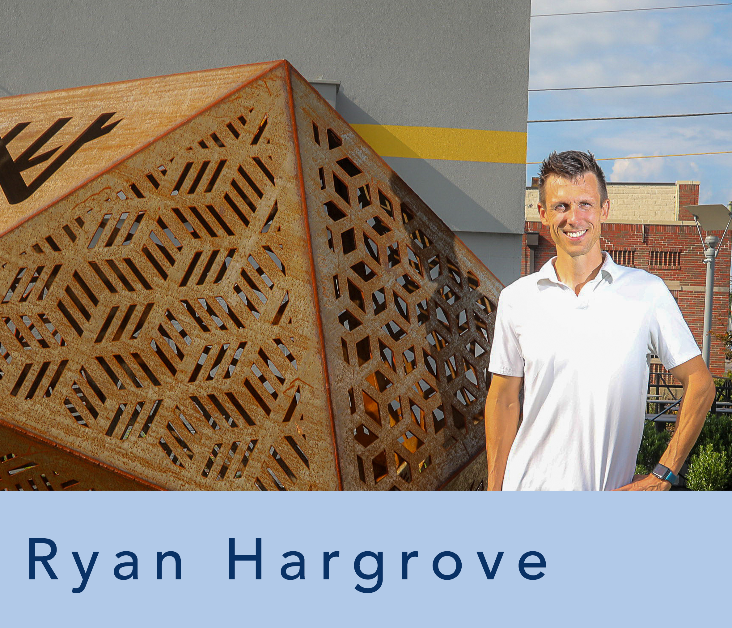 ryan hargrove standing by metal sculpture